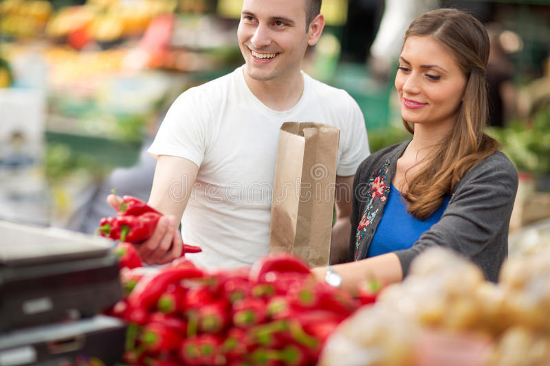 Couple shopping red pepper in grocery store stock image