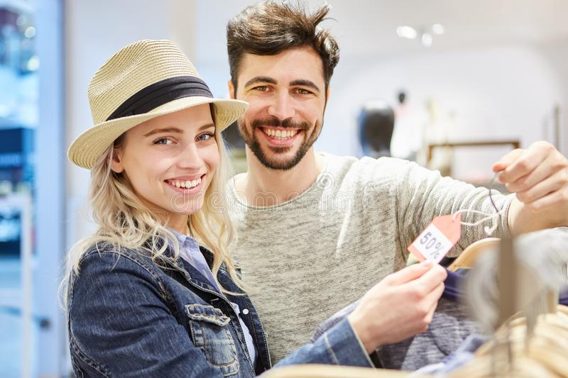 Couple shopping for special offers. Young happy couple shopping for clothes is looking for special offers stock photography