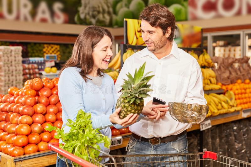 Couple in the supermarket uses smartphone app. Couple shopping at the supermarket uses smartphone app for product comparison stock photography