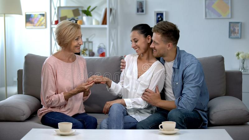Couple showing engagement ring to future mother-in-law, happy family relations stock photo