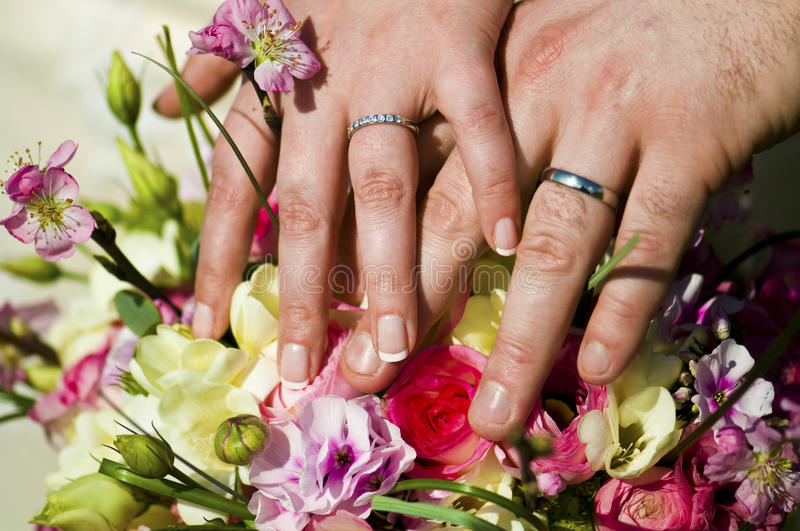 Couple showing off Wedding Rings. Description: Couple holding hands showing off thier Wedding Rings over a bouquet of flowers royalty free stock photos