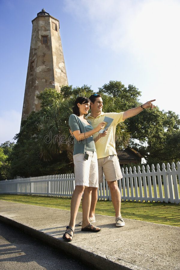 Couple sightseeing by lighthouse. Mid-adult Caucasian couple sightseeing with lighthouse in background at Bald Head Island, North Carolina royalty free stock images