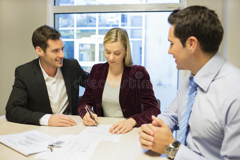 Couple signing real-estate contract stock photography