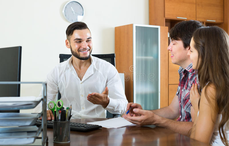 Couple signs a contract with smiling salesman. Young merried couple signs a contract with smiling salesman in the office stock photos