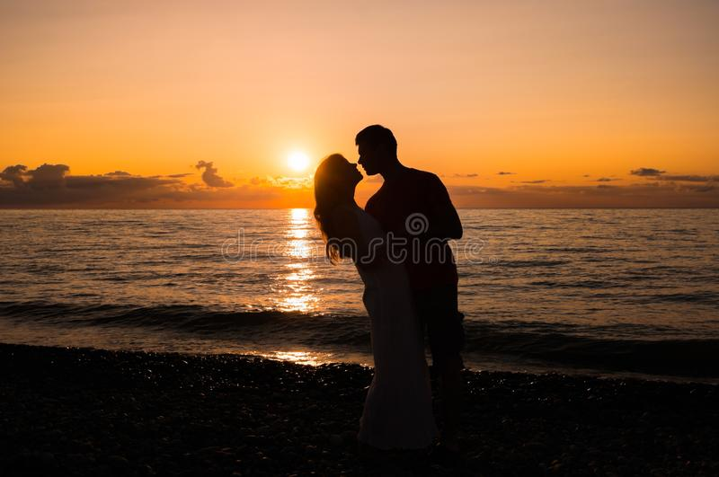 Couple silhouette on the beach at sunset royalty free stock images