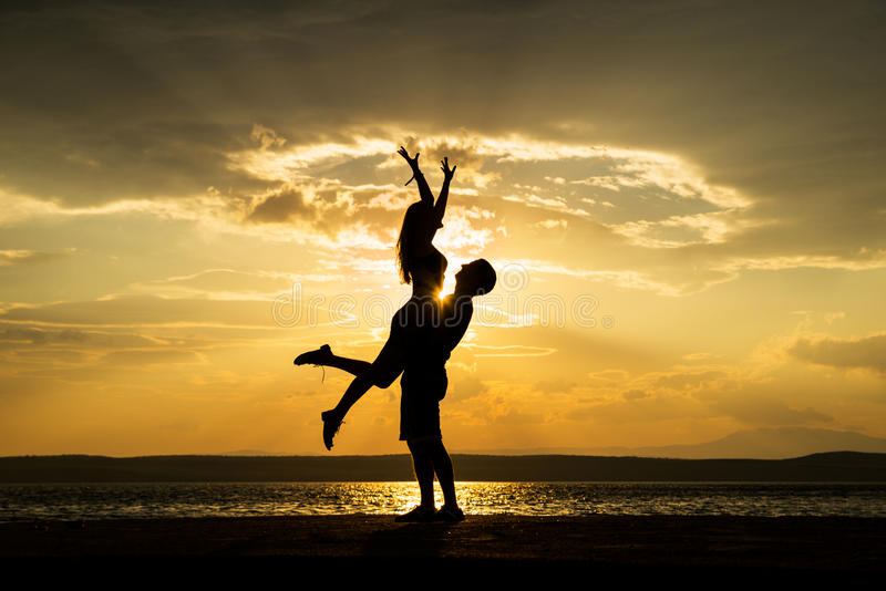 Couple silhouette dancing at the beach stock photos