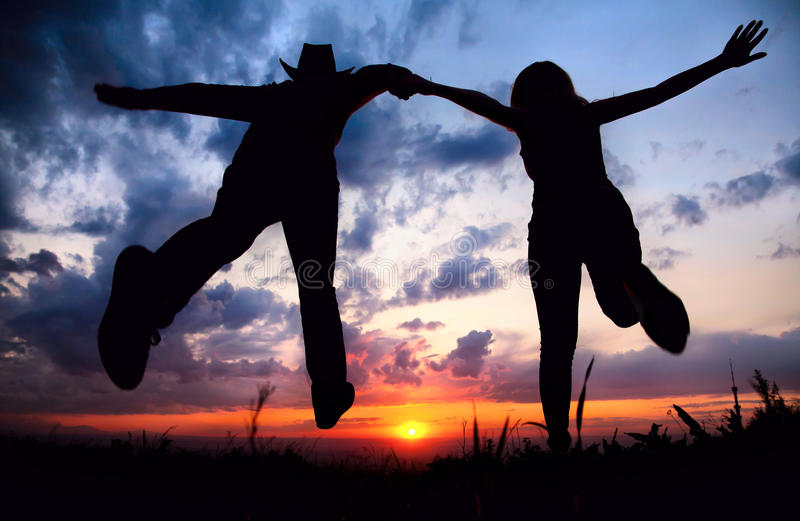 Couple silhouette running to the sunset stock photography