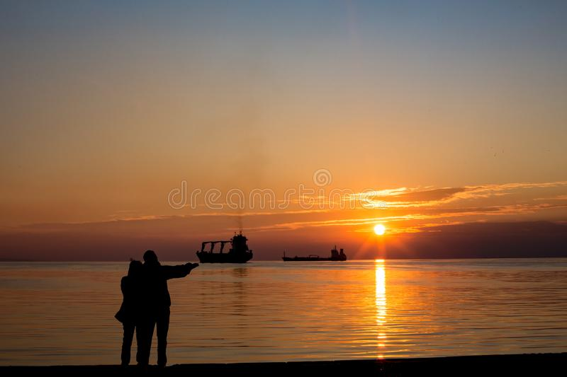 Couple silhouette by the sea. Two person, couple point the sun, silhouette by the sea at sunset with water reflections and ship, golden hour calmness royalty free stock images