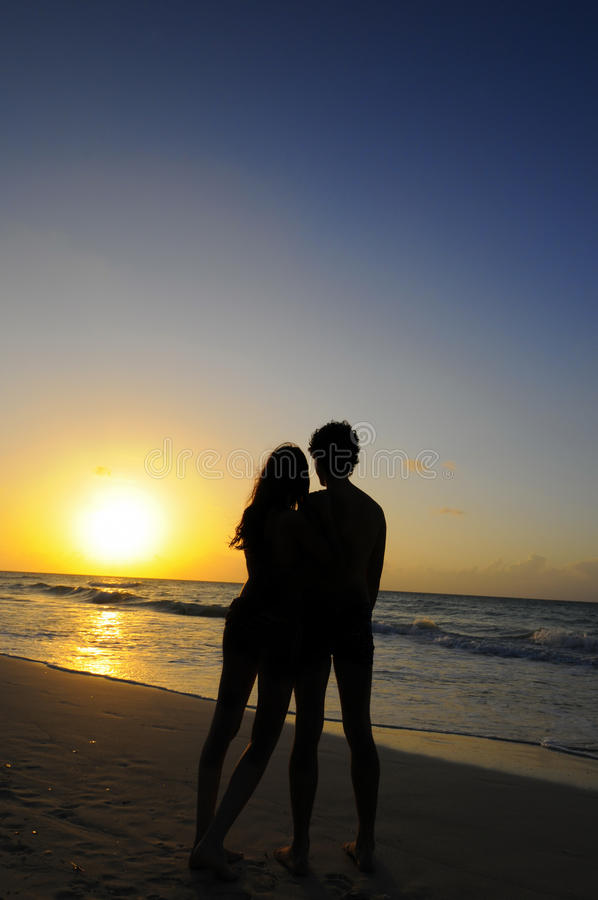 Couple silhouette on sunset ocean. Young couple silhouette embracing on sunset ocean background royalty free stock images