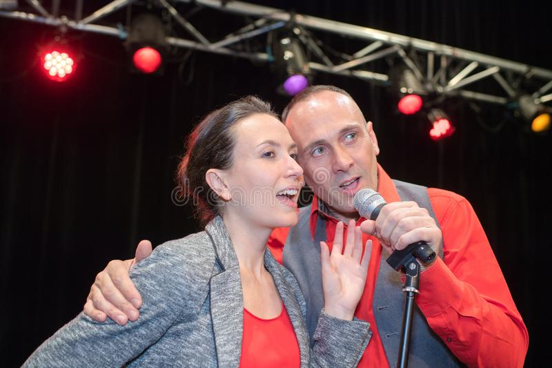 Couple singing on stage. Couple royalty free stock images