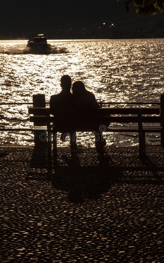 Silhouette couple on bench. A couple sit on a bench looking out onto Lake Como as a boat approaches stock photo