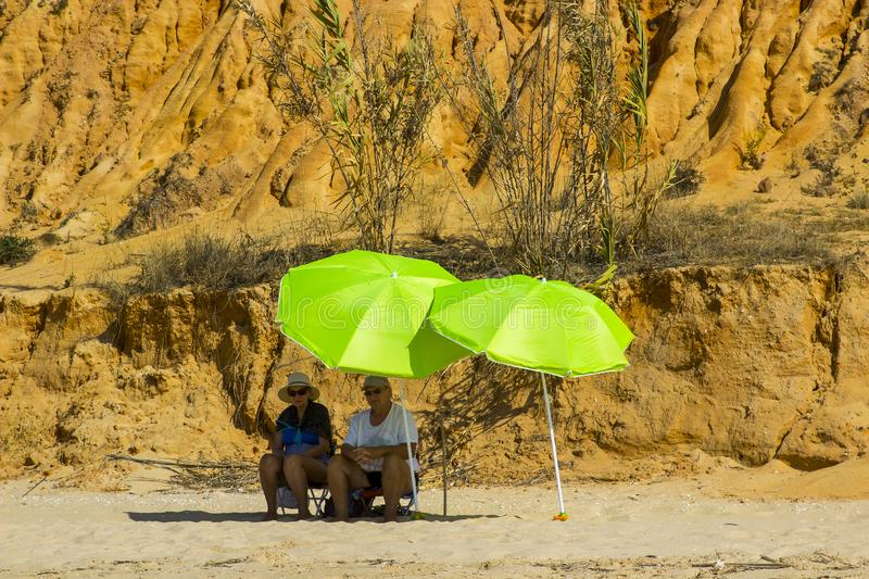 A couple sit in the shade of a brolly on a beach in Portugal stock photos