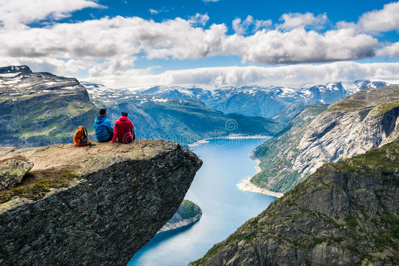 Couple sitting against amazing nature view on the way to Trolltunga. Location: Scandinavian. Mountains, Norway, Stavanger. Artistic picture. Beauty world. The stock photography