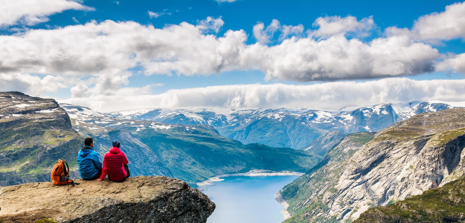 Couple sitting against amazing nature view on the way to Trolltunga. Location: Scandinavian. Mountains, Norway, Stavanger. Artistic picture. Beauty world. The stock photos