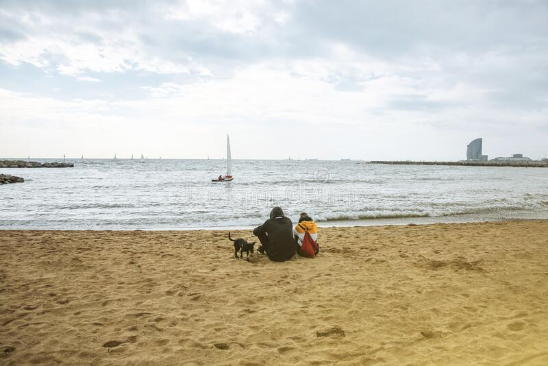 Couple is sitting at the autumn beach. Dog is walking on the sand. Atmosphere photo. Barceloneta. Man and woman in love.  royalty free stock photos