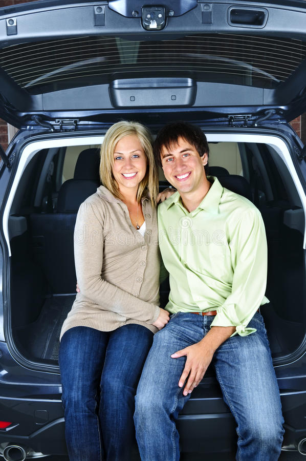 Couple sitting in back of car. Happy young couple sitting at back of car stock images