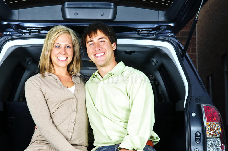 Couple sitting in back of car. Happy young couple sitting at back of car royalty free stock image