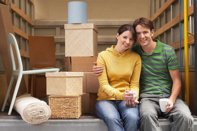 Couple Sitting Back Of Moving Van. Portrait of smiling young couple sitting back of moving van royalty free stock photography