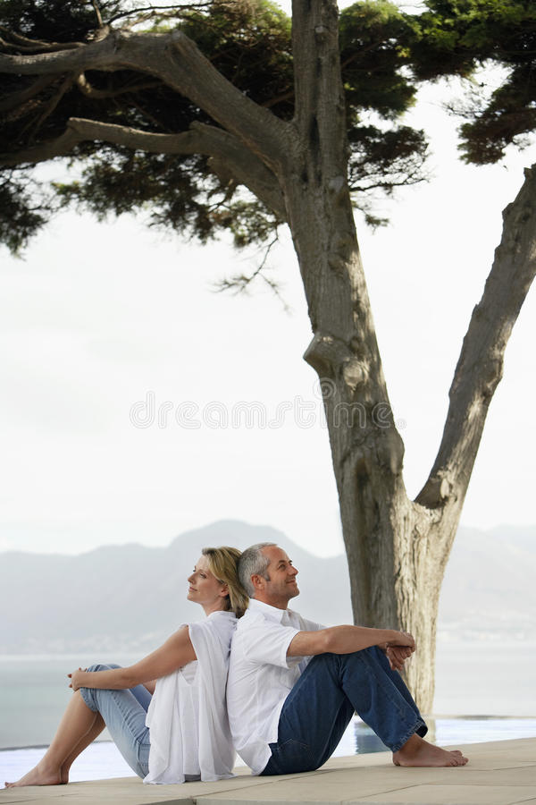 Download Couple Sitting Back To Back Stock Photo - Image: 29657684