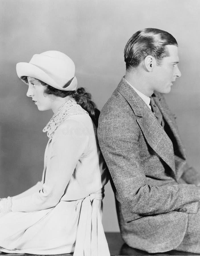 Couple sitting back to back royalty free stock image