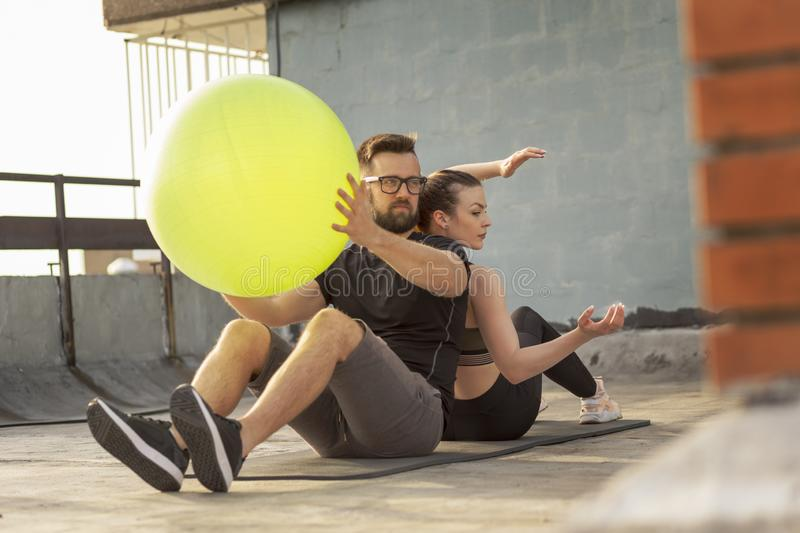 Couple working out with a pilates ball. Couple sitting back to back on a yoga mat on a building rooftop terrace, exercising by passing the pilates ball to each stock photography