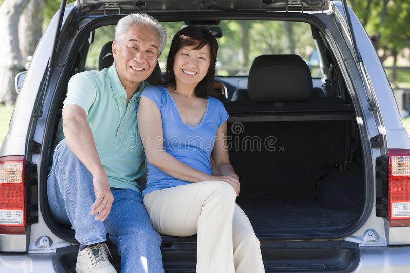 Couple sitting in back of van smiling. Looking at camera royalty free stock photo