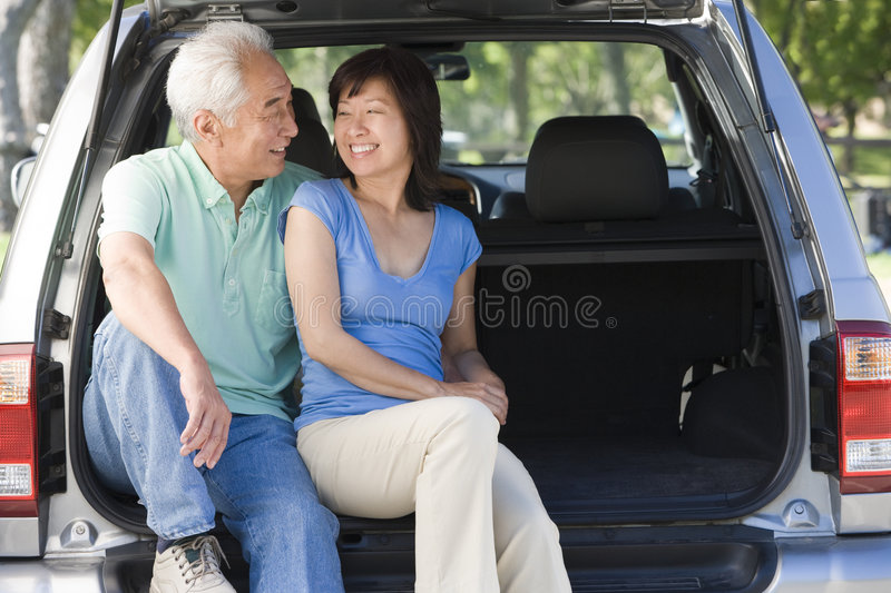 Couple sitting in back of van smiling. At each other royalty free stock photo