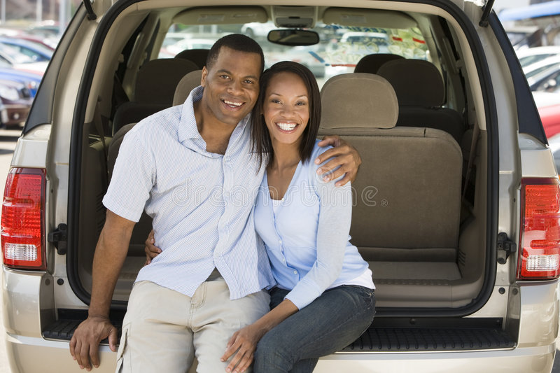 Couple sitting in back of van smiling.  stock photo