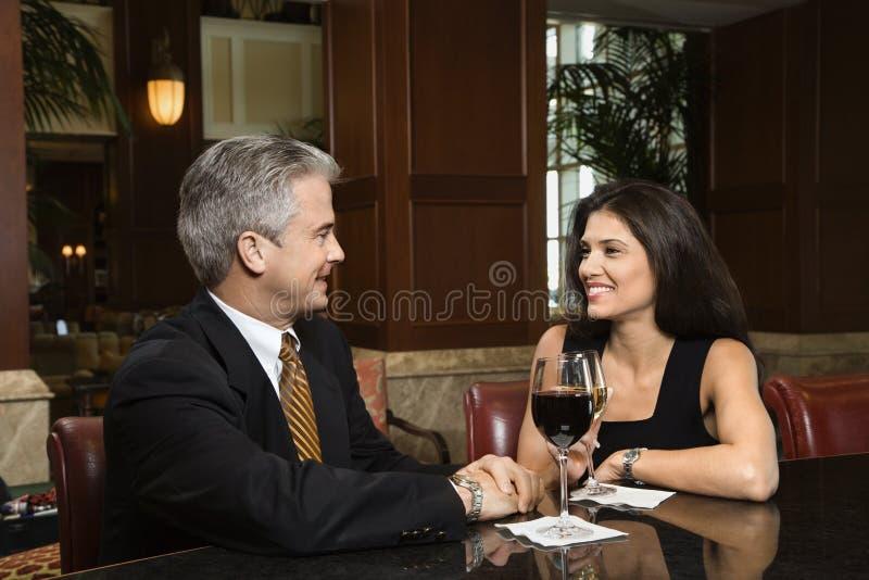 Couple sitting at bar. stock photo