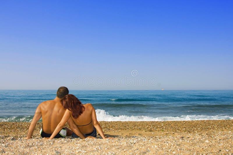 Couple sitting on the beach stock photos