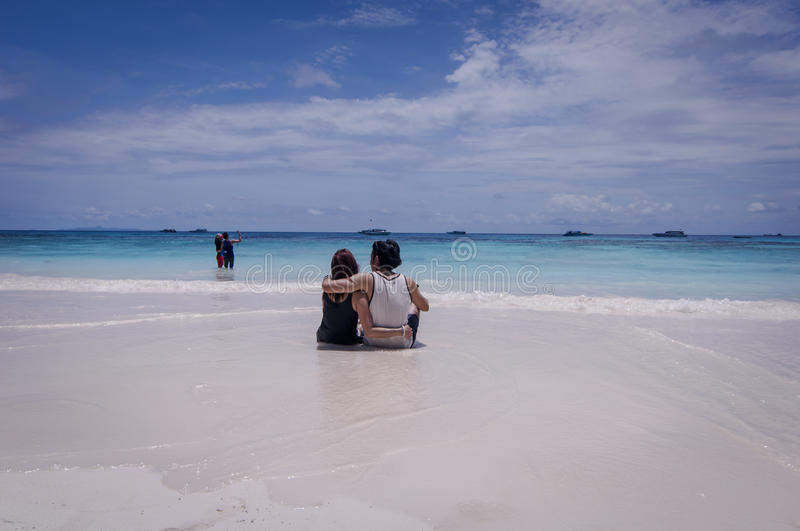 Couple sitting on beach, Koh Tachai Island,Thailand royalty free stock photography