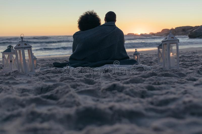 Couple sitting on the beach at sunset. Rear view of couple sitting on the beach wrapped in a blanket looking at the sunset. Couple looking the sunset from beach royalty free stock image
