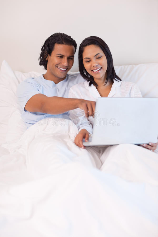 Download Couple Sitting On The Bed With Their Notebook Stock Image - Image: 22345775