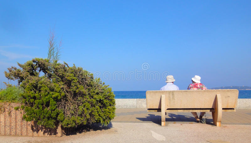 Couple sitting on a bench. Close to one of the beautiful beaches of Sainte Maxime, located on the French Riviera (Côte d'Azur) near Saint Tropez, in royalty free stock photo