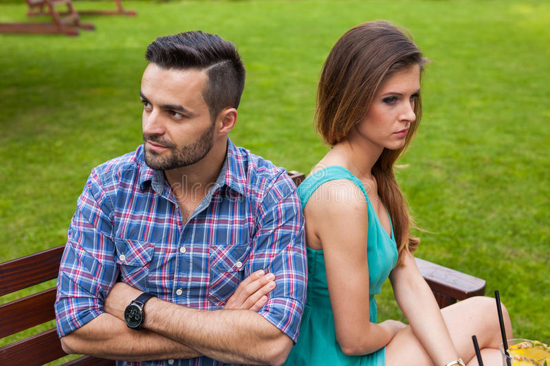 Couple sitting on the bench in the garden. They are taking offense and sitting back to back royalty free stock images