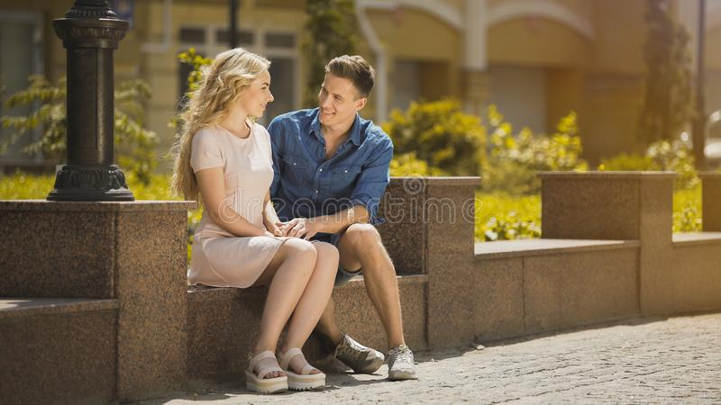 Couple sitting on bench, guy admiring blonde girl at first date, romantic mood royalty free stock photos