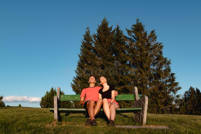 Couple sitting on bench in the mountains watching the sunset and taking a tan stock photography