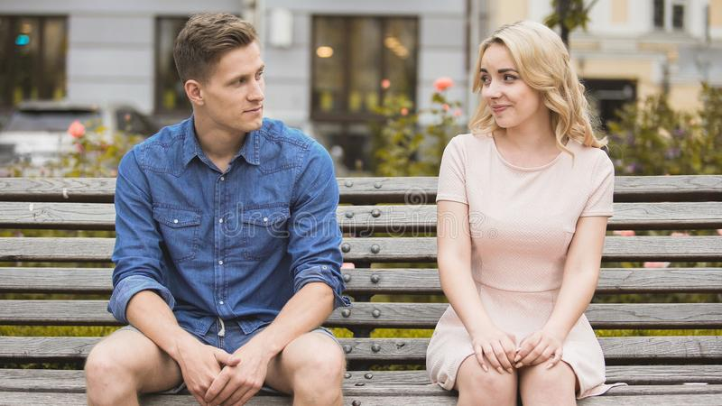 Couple sitting on bench and smiling at each other, reconciliation after fight royalty free stock image
