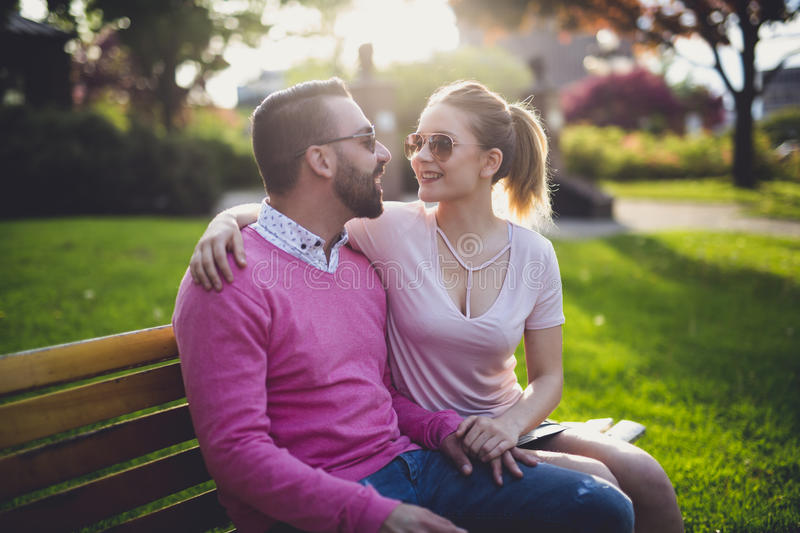 Couple sitting on a bench at the sunset in the city. A Couple sitting on a bench at the sunset in the city royalty free stock photo