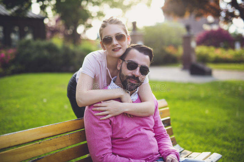 Couple sitting on a bench at the sunset in the city. A Couple sitting on a bench at the sunset in the city royalty free stock photography