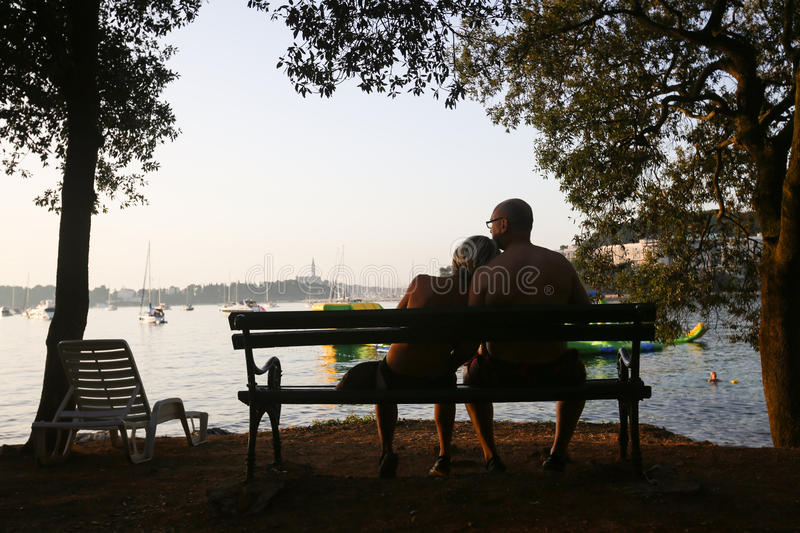 Couple sitting on bench at sunset. ROVINJ, CROATIA - AUGUST 3 : A rear view of a couple sitting on a wooden bench on the shore and watching the sunset on royalty free stock photos