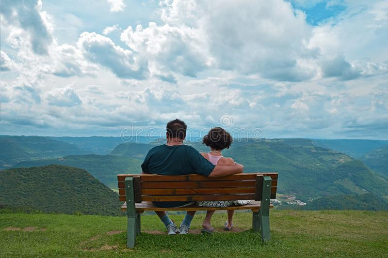 Couple Sitting on Brown Wooden Bench Near Mountains Covered With Grasses Under Blue Cloudy Sky royalty free stock image