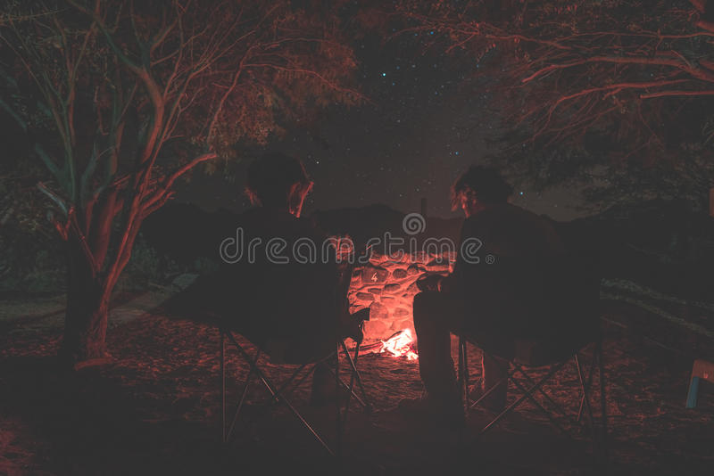 Couple sitting at burning camp fire in the night. Camping in the forest under starry sky, Namibia, Africa. Summer adventures and stock photos