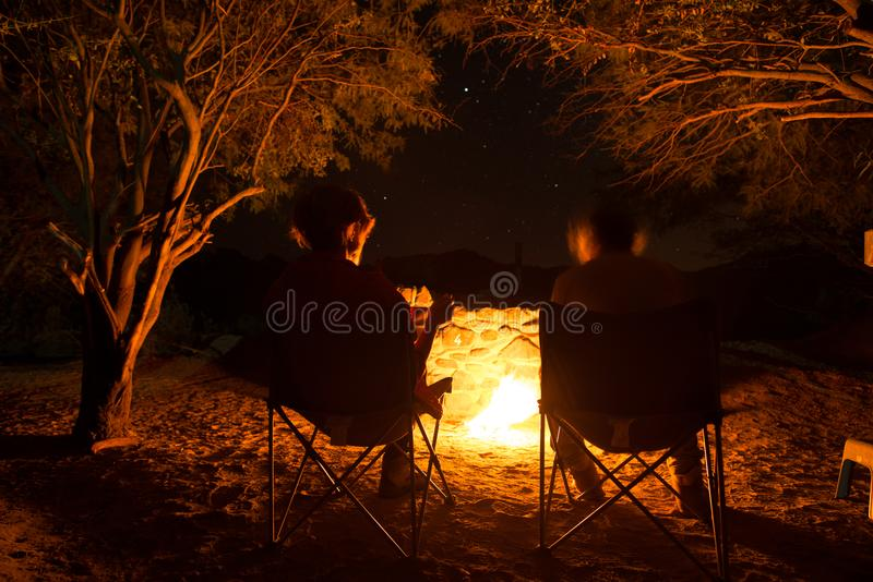Couple sitting at burning camp fire in the night. Camping in the forest under starry sky, Namibia, Africa. Summer adventures and e. Xploration in the african royalty free stock image