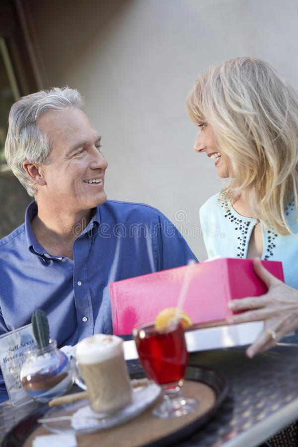 Couple sitting at cafe table on Shopping Trip. Wife opening gift royalty free stock photo