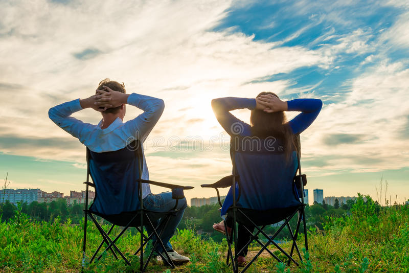 Couple sitting in chairs and admire the sunrise. Over the city stock images