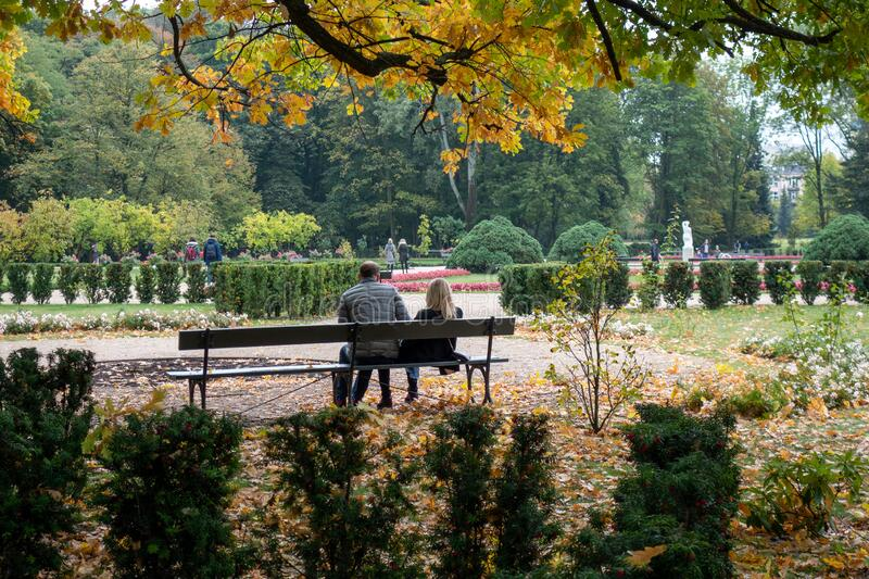 Couple sitting and chatting on the bench in the Lazienki  park royalty free stock photo