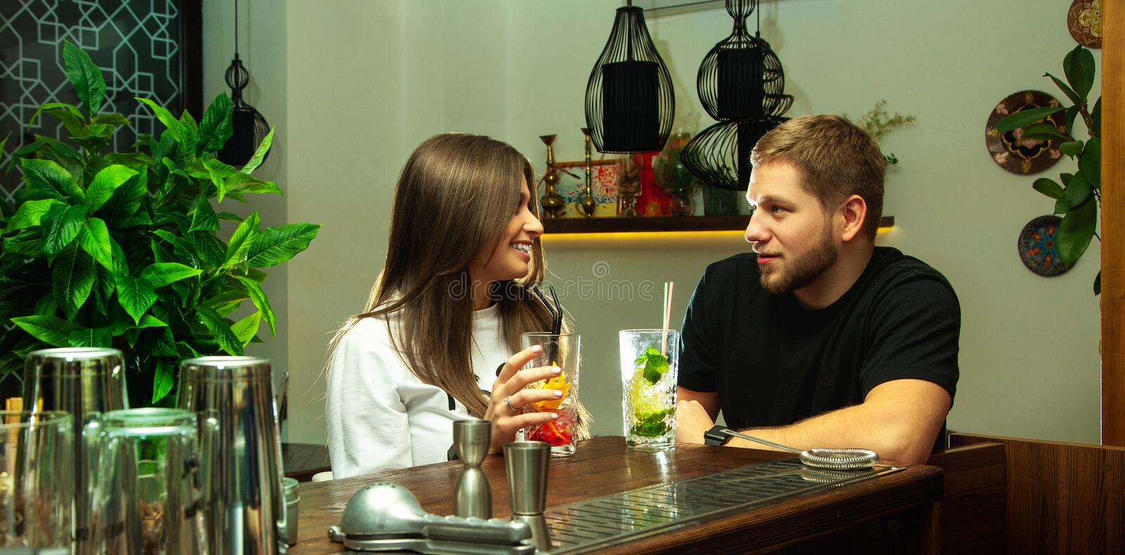 Couple sitting with cocktails at the bar stock image