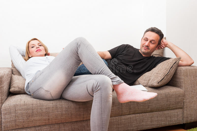 Couple sitting on the couch after a dispute stock photo