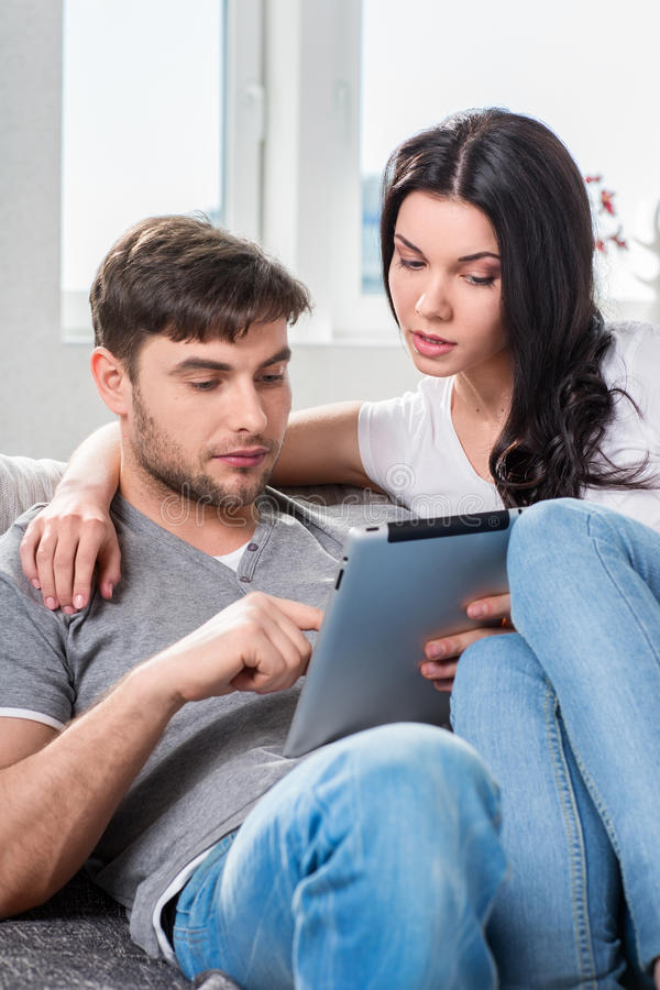 Download Couple Sitting On A Couch With Tablet Computers Stock Photo - Image: 33031142